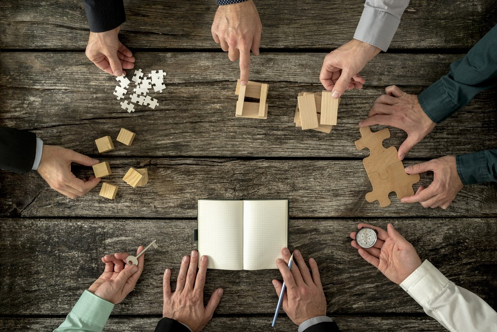 Eight businessmen planning a strategy in business advancement each holding different but equally important metaphorical element - compass, puzzle pieces, pegs, cubes, key and one making notes.